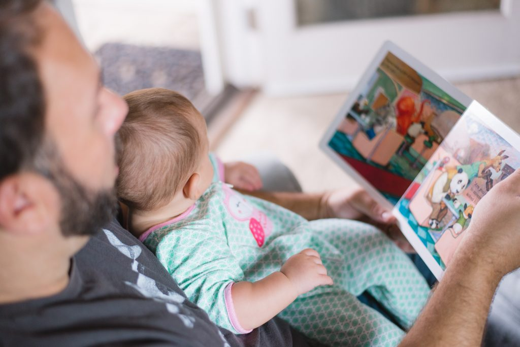 baby sitting on man's lap reading a book together