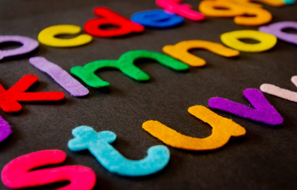 felt letters on black background; order to teach the alphabet