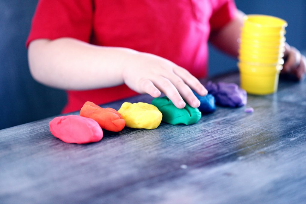 child's hands playing with colorful playdoh. mistakes to avoid when choosing a daycare