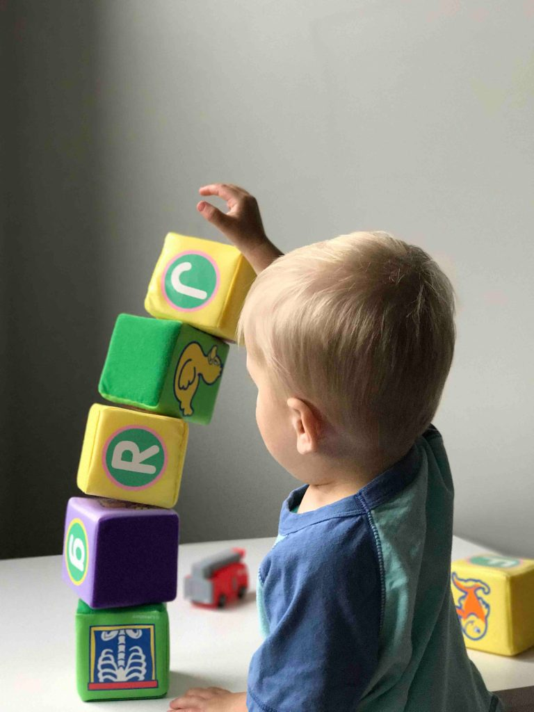 Boy stacking blocks with letters on them to develop literacy skills.