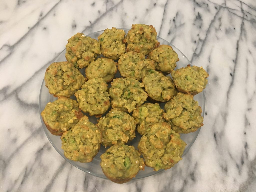A dairy free toddler finger food of banana, avocado, and apple mini muffins on a marble countertop.