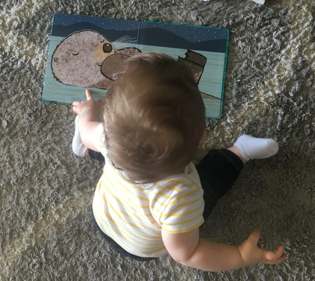 Toddler boy independently reading a book on a carpet.