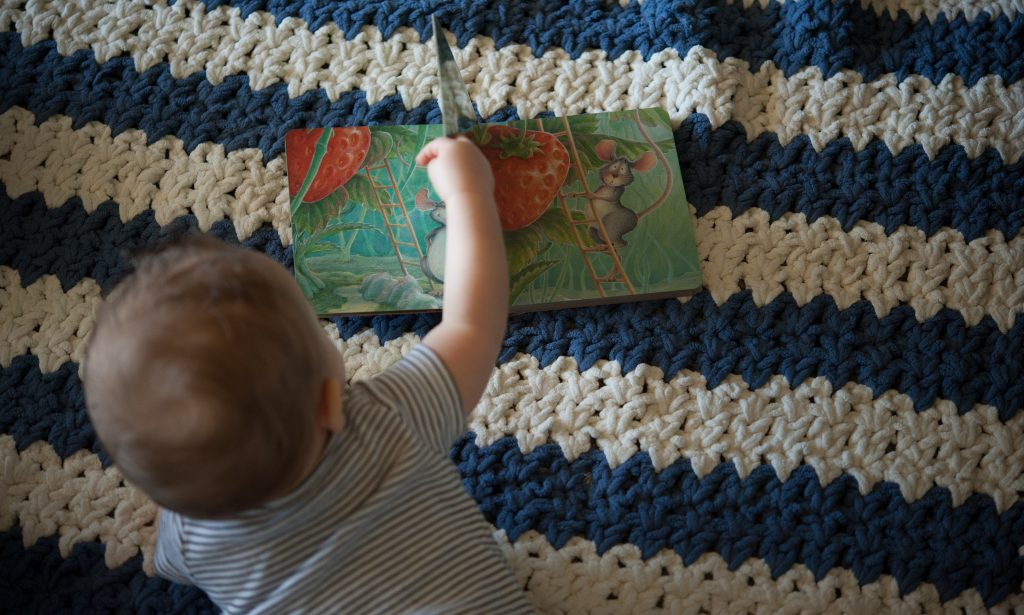Toddler boy reading a board book on a striped blanket.