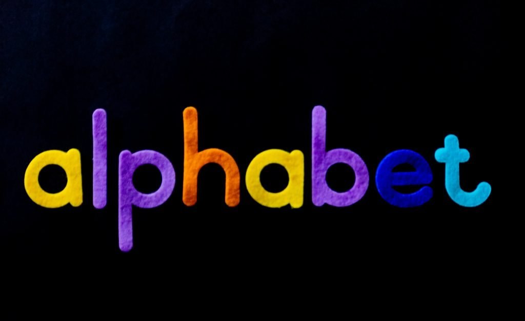 colorful felt alphabet letters on a black background; order to teach the alphabet