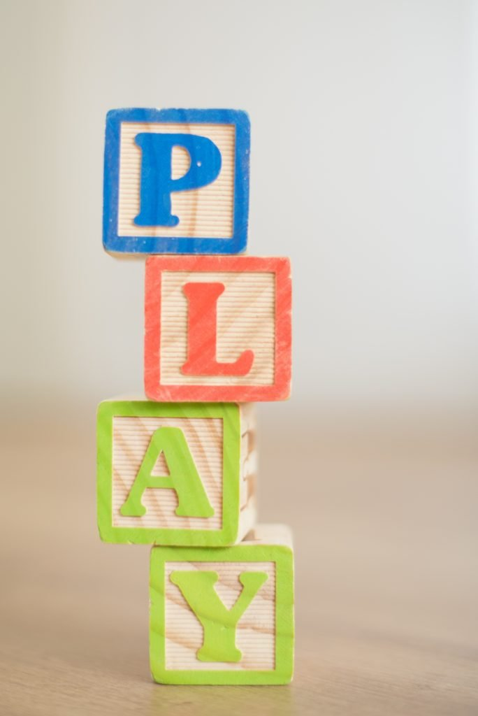 wooden letter blocks that spell out play; using play to teach your child the alphabet