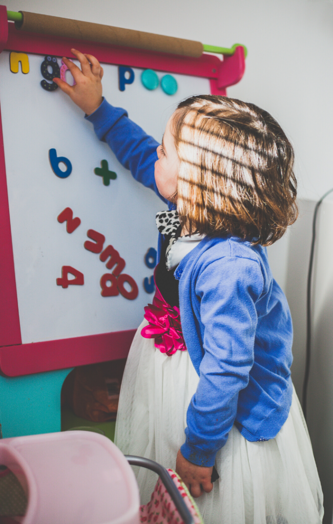 Little girl in tulle dress playing with magnetic letters on an easel.