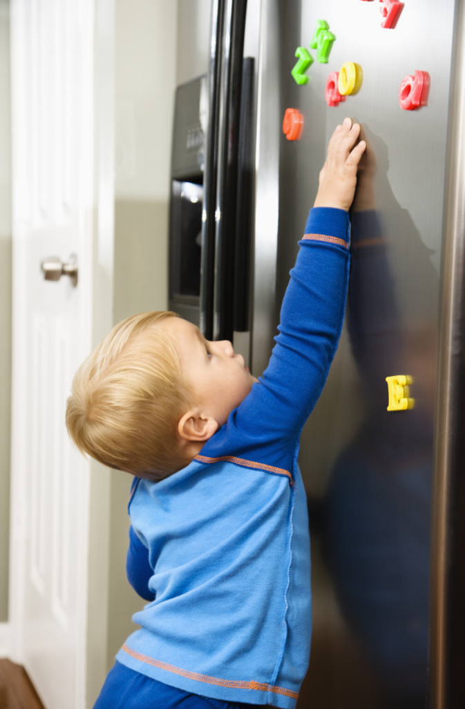 boy playing with magnetic letters on fridge