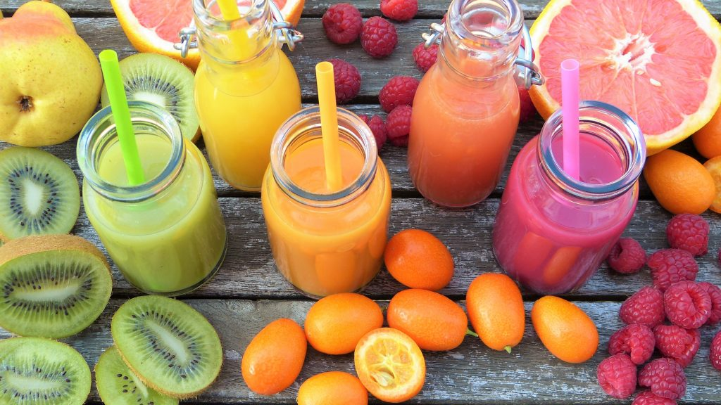 various colorful smoothies surrounded by colorful fruit