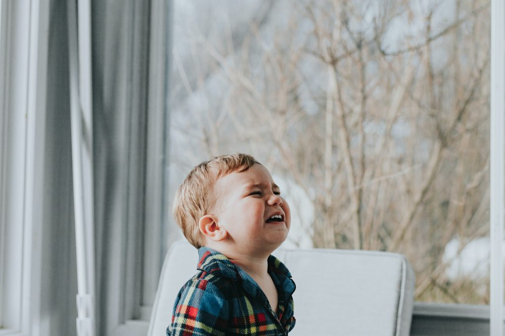 toddler boy crying by a window