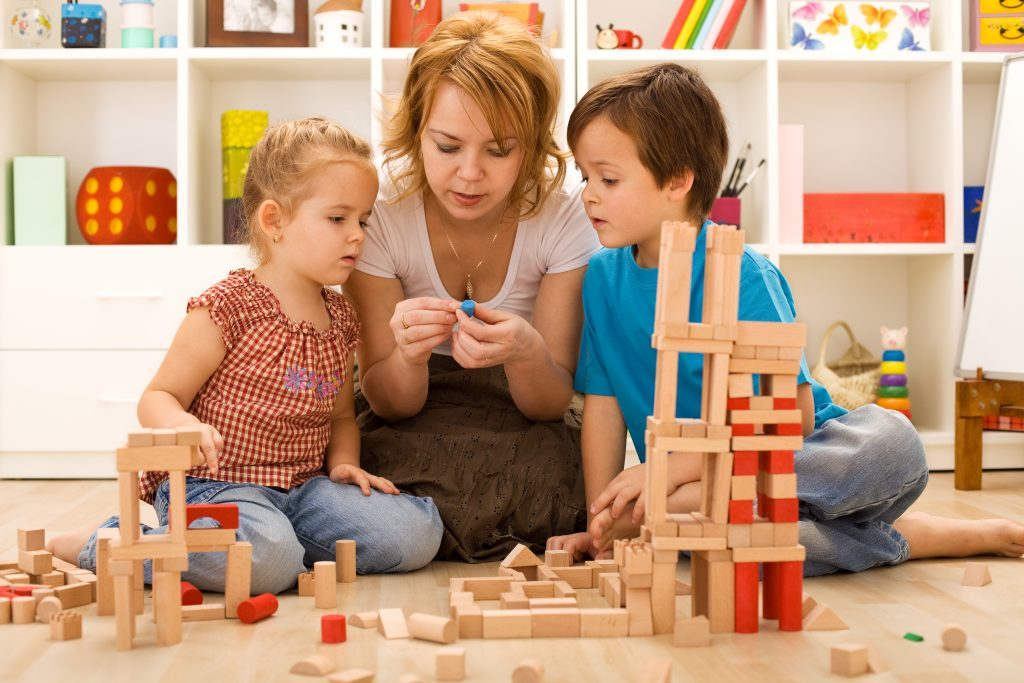mom playing blocks with her children
