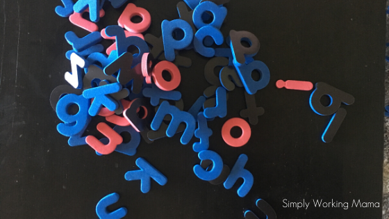 magnetic letters on a black table to help with learning through play