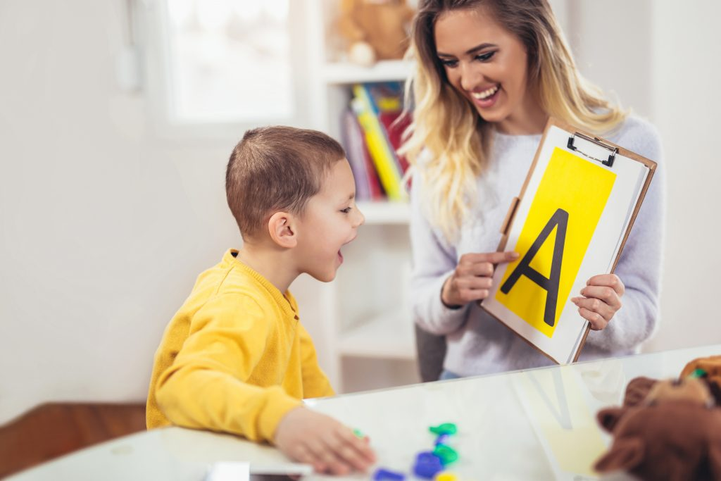 Woman showing a boy an uppercase letter a
