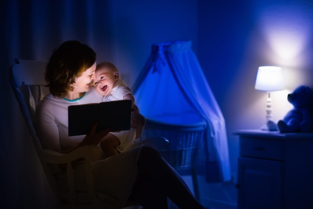 Mother and baby reading a book in dark bedroom. Mom and child read books before bed time. Family in the evening. Kids room interior with night lamp and bassinet. Parent holding infant next to crib. Read to your baby