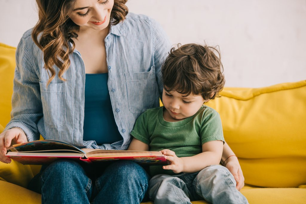 Mother and son sitting together and reading a book; how to read to toddlers