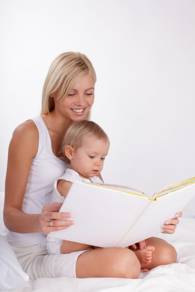Mother reading book to a daughter at home; read to your baby