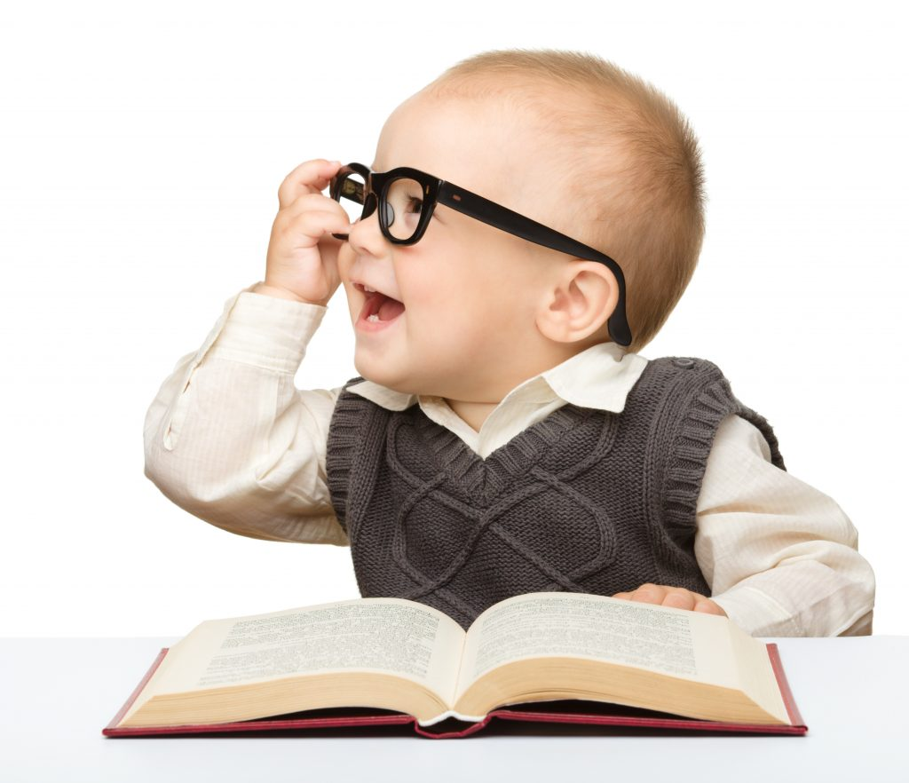 Cute little child play with book and glasses while sitting at table, isolated over white; read to your baby