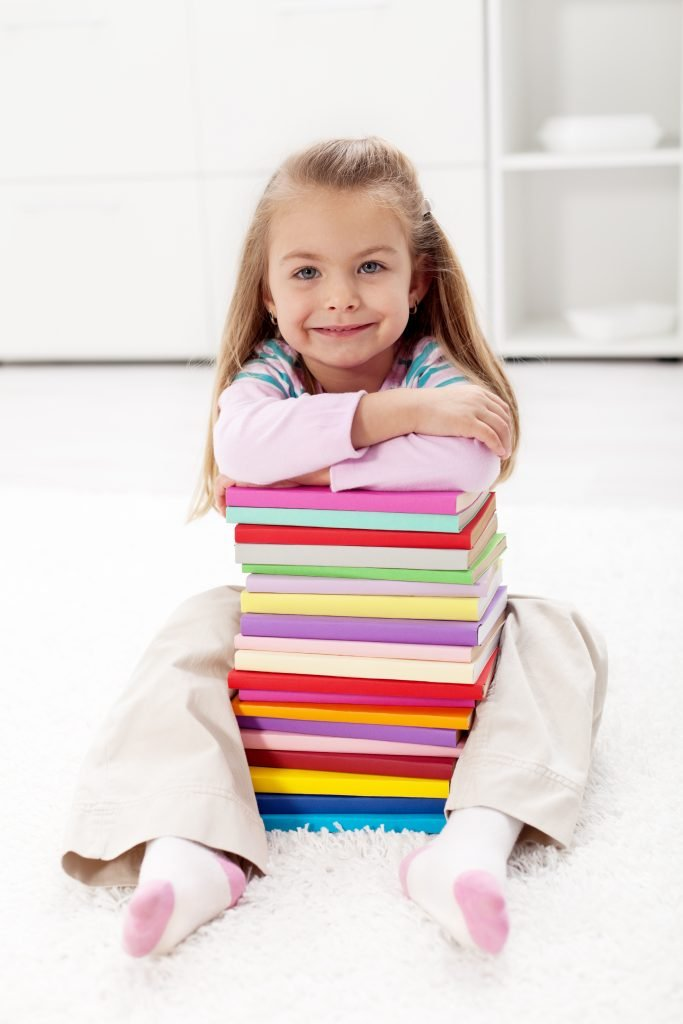 Young blonde girl resting on a stack of books; how to read to toddlers