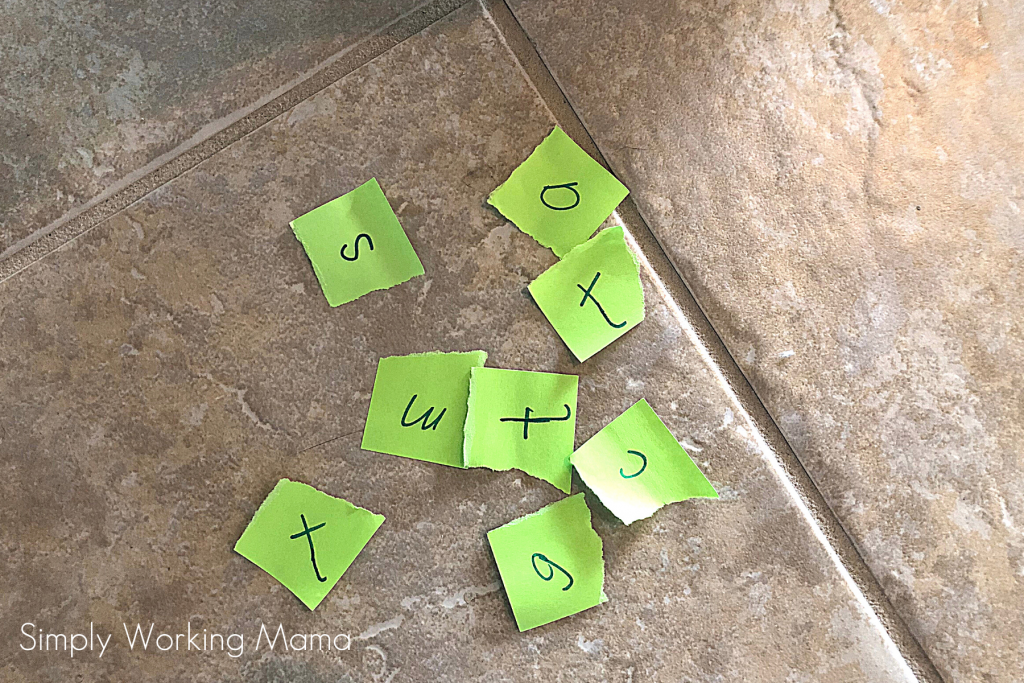 Letters written on cards on a tile floor; read and play