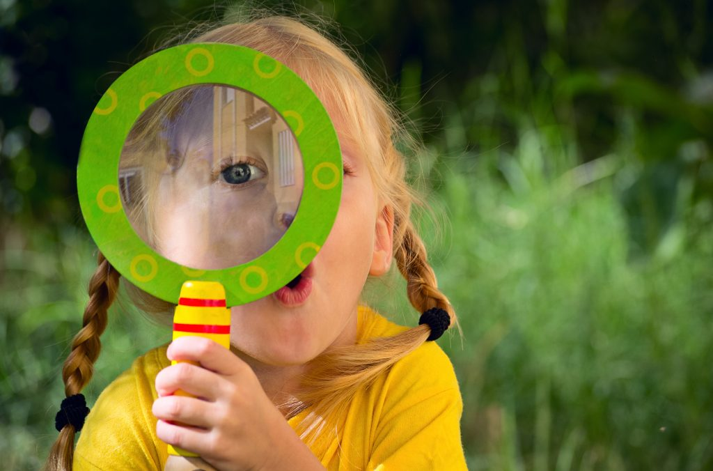 Toddler girl holding magnifying glass while learning through play
