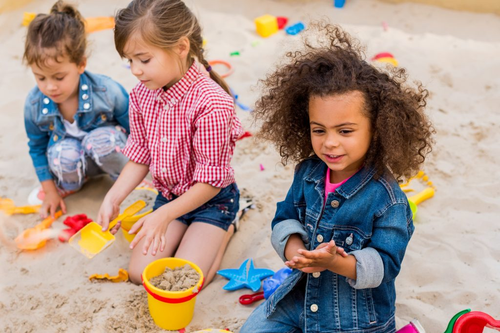 Preschool girls learning through play in a sandbox outside.