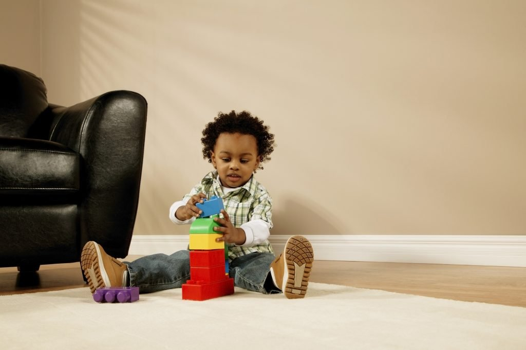Toddler boy learning through play with blocks
